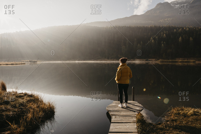 Switzerland- Engadine- Lake Staz- woman standing on a jetty at lakeside in morning sun