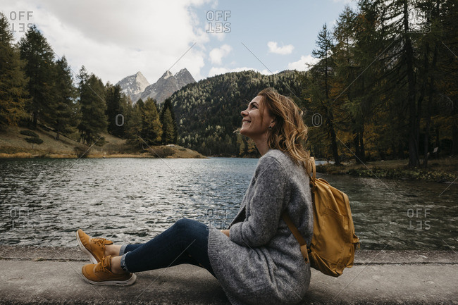 Switzerland- Grisons- Albula Pass- smiling woman on a hiking trip sitting at lakeside in mountainscape