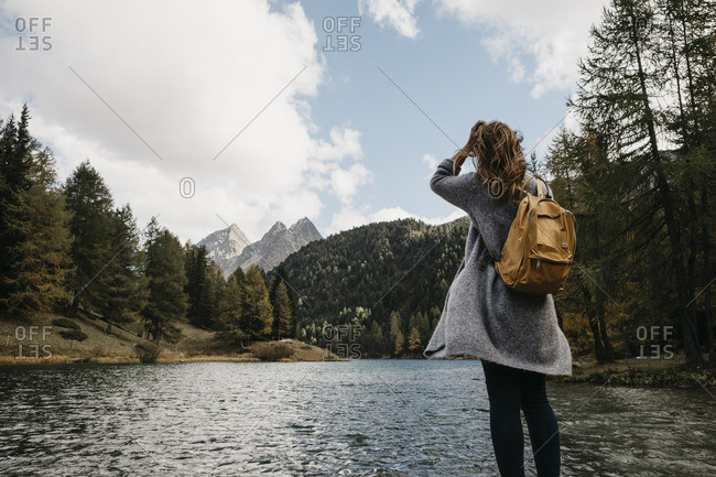 Switzerland- Grisons- Albula Pass- woman on a hiking trip standing at lakeside in mountainscape