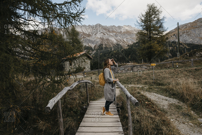 Switzerland- Engadin- woman on a hiking trip on a wooden bridge