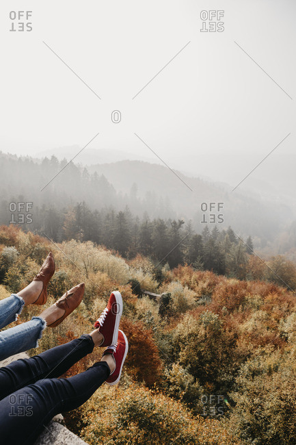 Germany- Black Forest- Sitzenkirch- legs of two women sitting at Sausenburg Castle above mountain forest