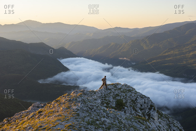Italy- Umbria- Sibillini National Park- hiker on viewpoint at sunrise