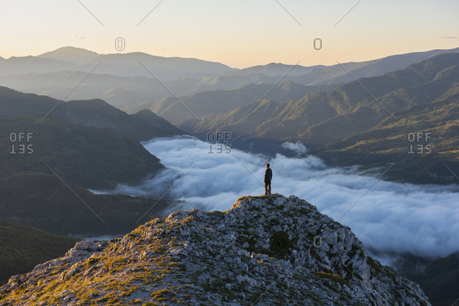Italy- Umbria- Sibillini National Park- hiker standing on viewpoint at sunrise