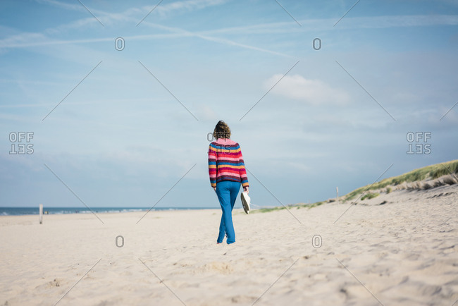 Mature woman walking barefoot on the beach