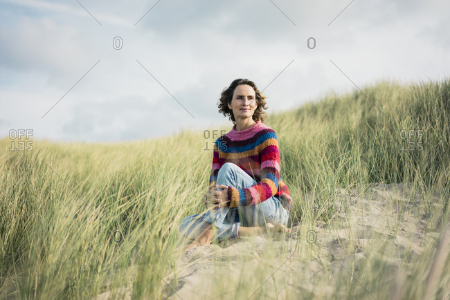 Mature woman relaxing on the beach- sitting in the dunes