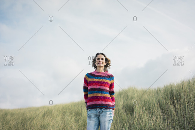 Content woman standing in the dunes- smiling