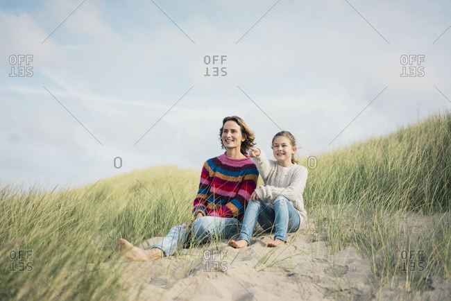 Mother and daughter sitting on a beach dune- girl pointing at distance- smiling