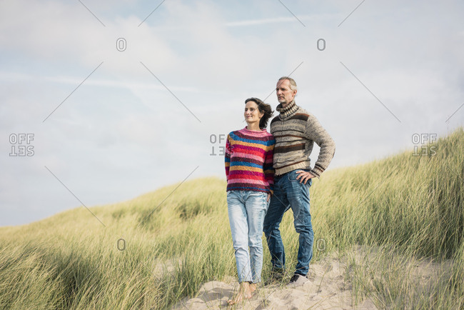 Mature couple standing in the dunes- with arms around