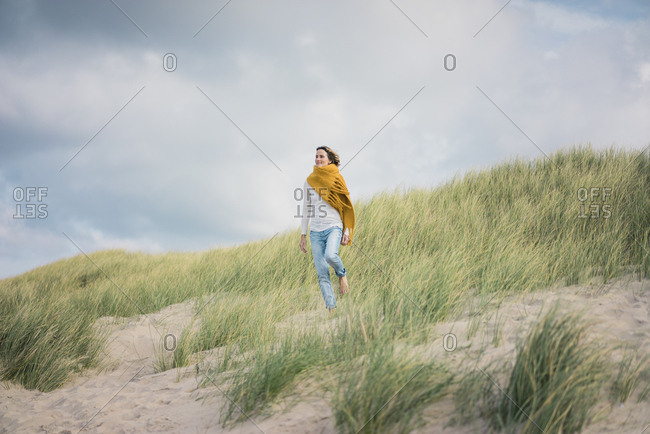 Mature woman relaxing in the dunes- enjoying the wind