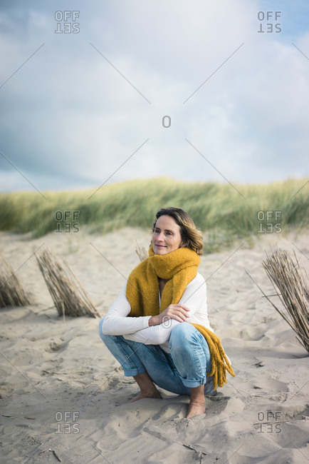 Mature woman crouching in the dunes- enjoying the wind