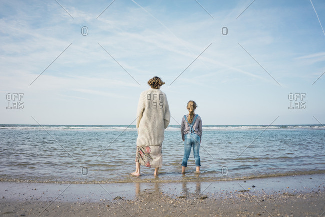 Mother and daughter standing on the beach- looking at the sea- rear view