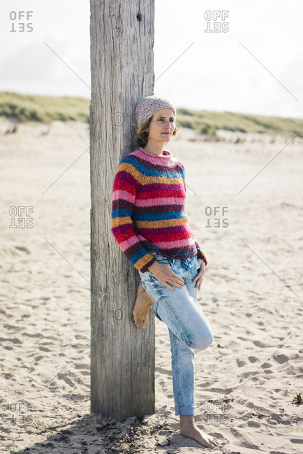 Mature woman relaxing on the beach- leaning on a pole