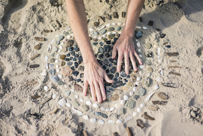 Mature woman making a heart from seashells on the beach