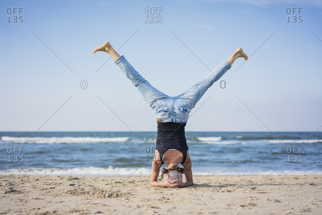 Mature woman doing a headstand on the beach
