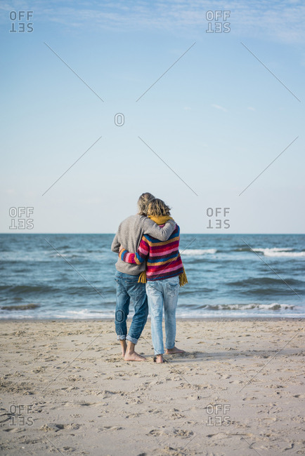 ture couple standing on the beach with arms around- looking at the sea