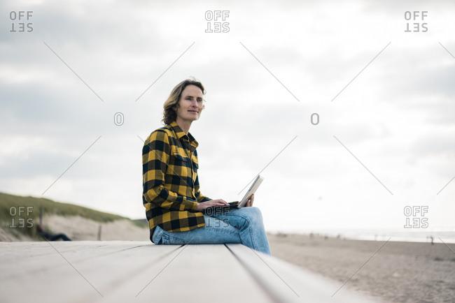 Mature woman sitting on boardwalk at the beach- using laptop