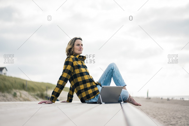 Mature woman sitting on boardwalk at the beach- using laptop