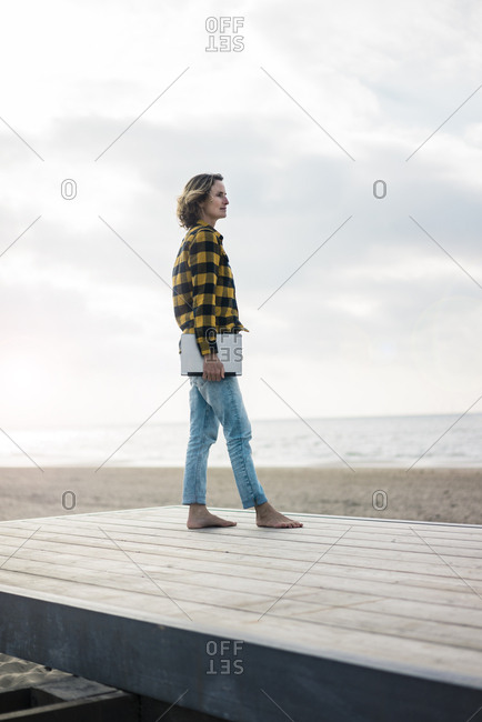 Mature woman standing on boardwalk at the beach- holding laptop