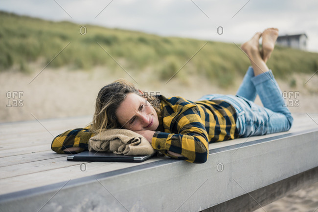 Mature woman with laptop- lying on boardwalk at the beach- relaxing