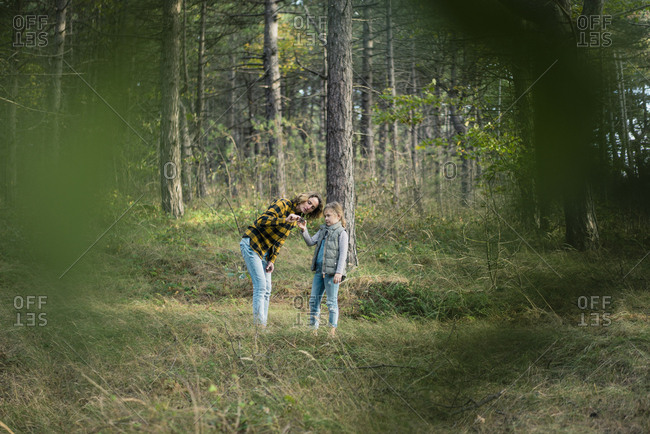 Mother and daughter exploring nature in the forest
