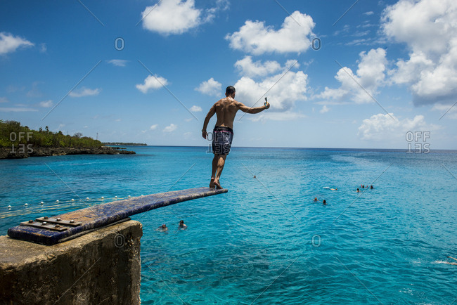 April 5, 2016: Carribean- Colombia- San Andres- man on diving board above turquoise water