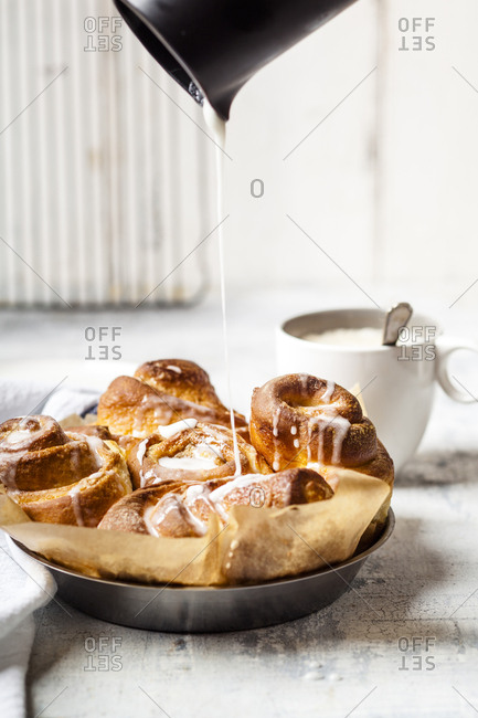 Garnishing home-baked cinnamon buns with icing sugar