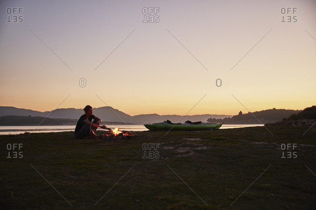 Chile- Talca- Maule River- woman sitting at camp fire beside canoe