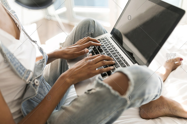 Close-up of woman sitting on bed using laptop