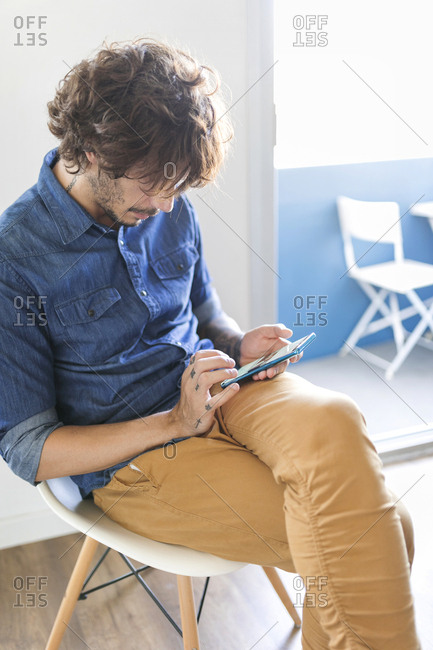 Man sitting on chair at home using cell phone