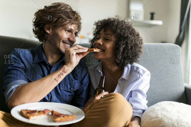 Happy couple sitting on couch eating pizza