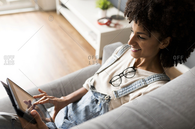 Smiling woman lying on couch at home using tablet