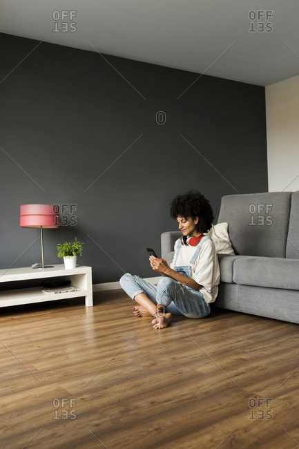 Smiling woman sitting at home with headphones and cell phone