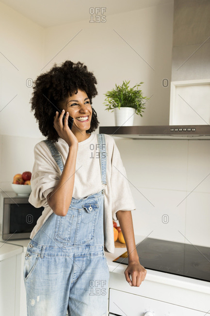 Happy woman on cell phone in kitchen at home