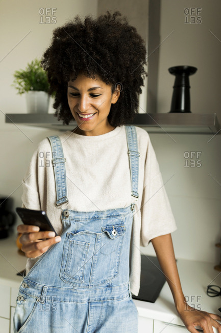 Smiling woman using cell phone in kitchen at home