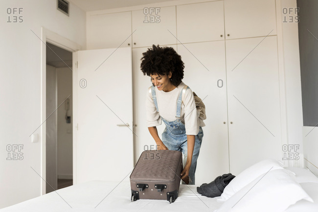 Smiling woman placing suitcase on bed