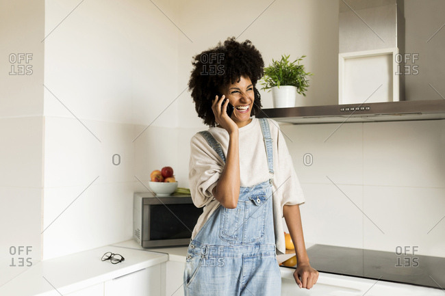 Laughing woman on cell phone in kitchen at home
