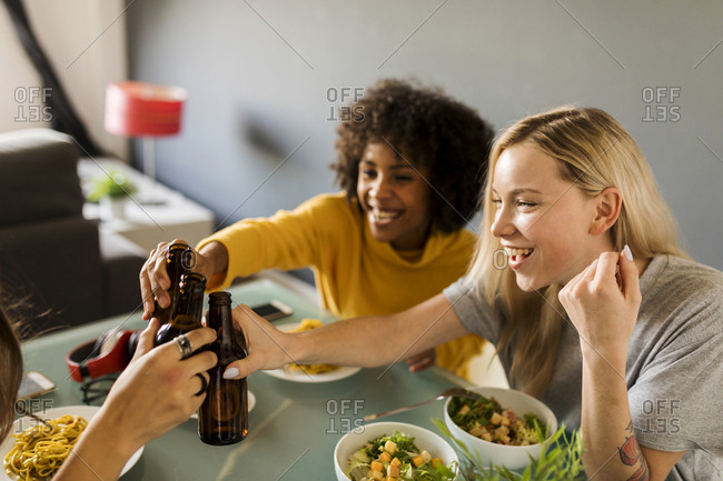 Happy girlfriends sitting at dining table clinking beer bottles