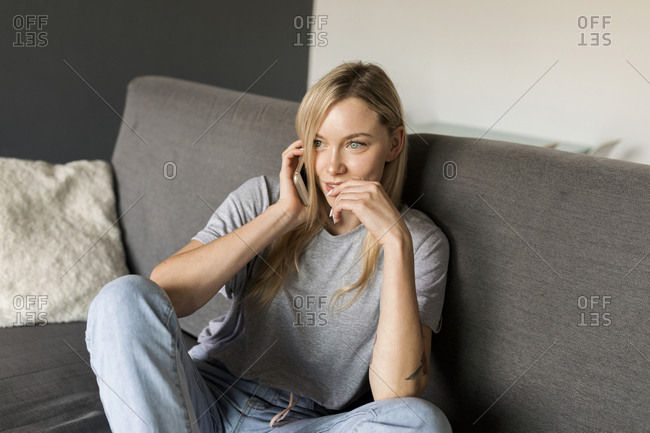 Smiling young woman sitting on couch talking on cell phone