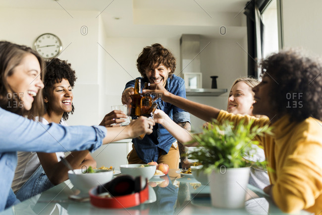 Cheerful friends clinking beer bottles at dining table