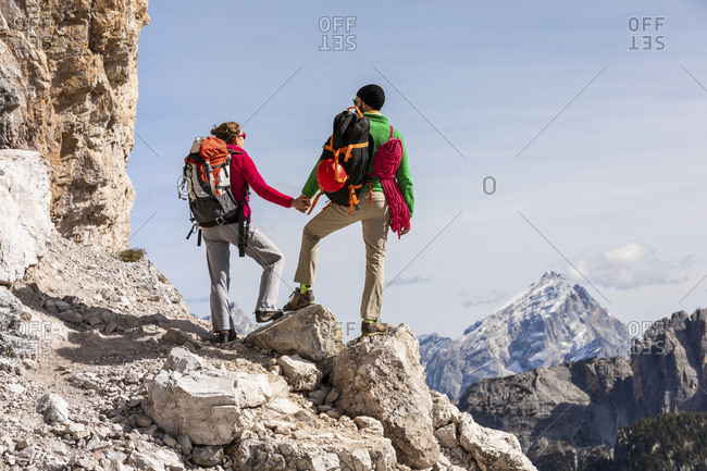 Italy- Cortina d'Ampezzo- couple with rope and climbing equipment holding hands and looking at view