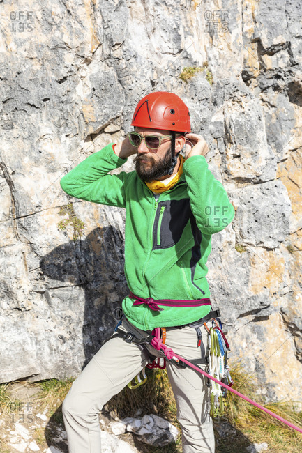 Italy- Cortina d'Ampezzo- man getting ready for climbing in the Dolomites mountains