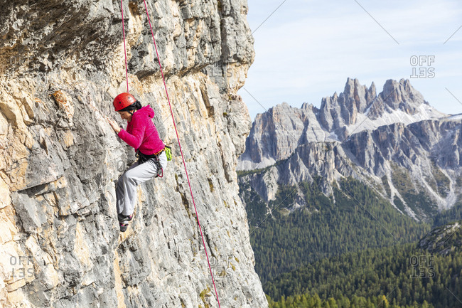 Italy- Cortina d'Ampezzo- woman climbing in the Dolomites mountains
