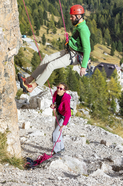 Italy- Cortina d'Ampezzo- man abseiling in the Dolomites mountains with the assistance of a woman