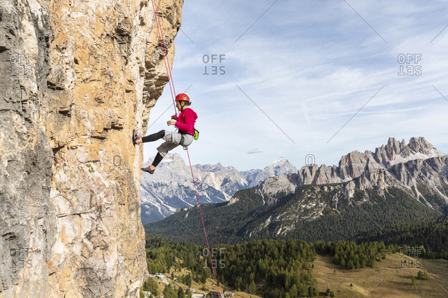 Italy- Cortina d'Ampezzo- woman abseiling in the Dolomites mountains