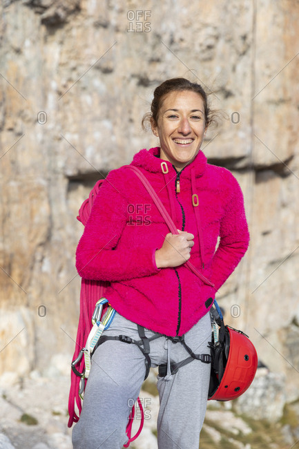 Italy- Cortina d'Ampezzo- portrait of a happy woman with climbing equipment in the Dolomites mountains