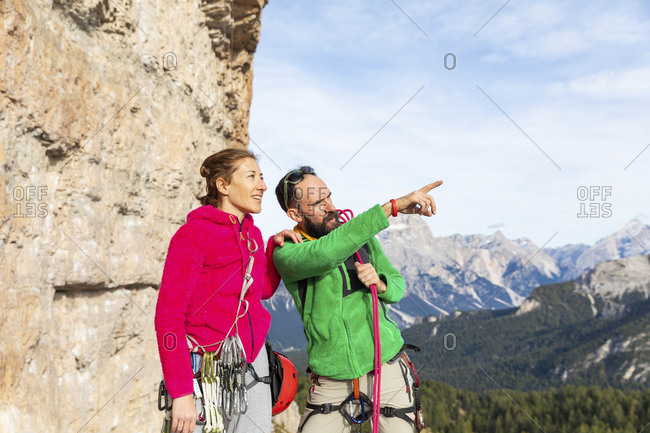 Italy- Cortina d'Ampezzo- couple with climbing equipment looking at view an talking in the Dolomites mountains