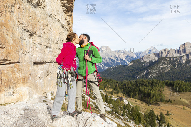 Italy- Cortina d'Ampezzo- couple with climbing equipment kissing in the Dolomites mountains