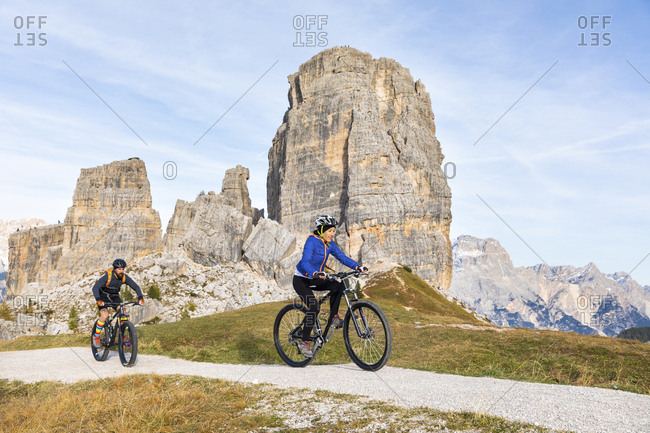 Italy- Cortina d'Ampezzo- two people cycling with mountain bikes in the Dolomites mountains