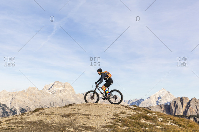 Italy- Cortina d'Ampezzo- man cycling with mountain bike in the Dolomites mountains