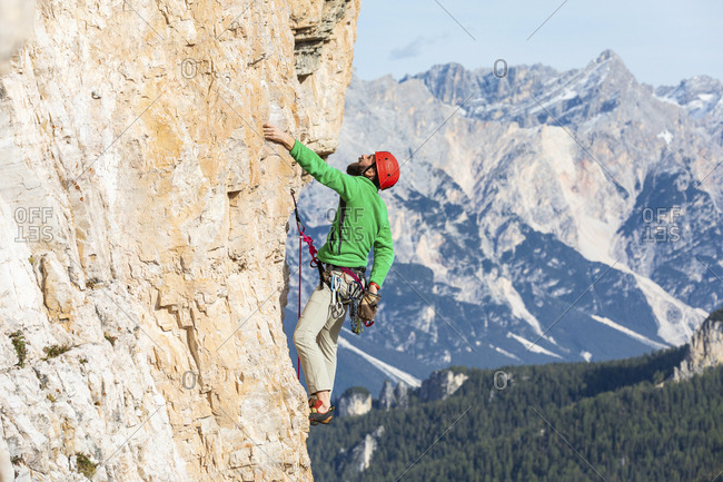 Italy- Cortina d'Ampezzo- man using chalk powder while climbing in the Dolomites mountains